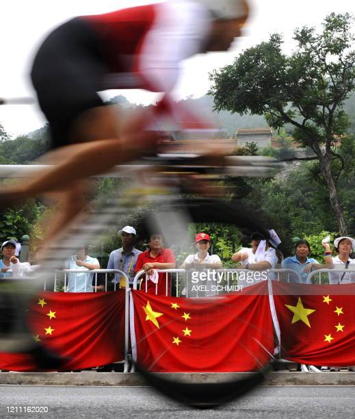 Switzerland's Priska Doppmann races past spectators with Chinese flags during the women's road cycling individual time trial event during the 2008...