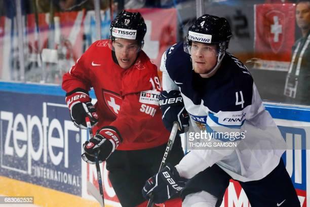 Switzerland's Reto Schappi vies for the puck with Finland's Mikko Lehtonen during the IIHF Men's World Championship group B ice hockey match between...