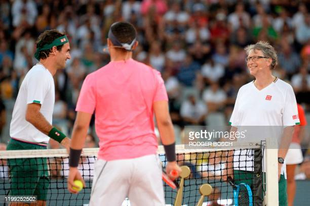 Switzerland's Roger Federer and American philanthropist Bill Gates reacts after a point against South African Comedian Trevor Noah and Spain's Rafael...