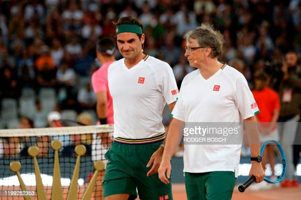 Switzerland's Roger Federer and American philanthropist Bill Gates walks ont the tennis court during their double's tennis match against Spain's...