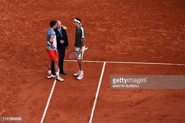 Switzerland's Roger Federer and Switzerland's Stanislas Wawrinka speak with a member of staff in order to stop the game due to weather conditions...
