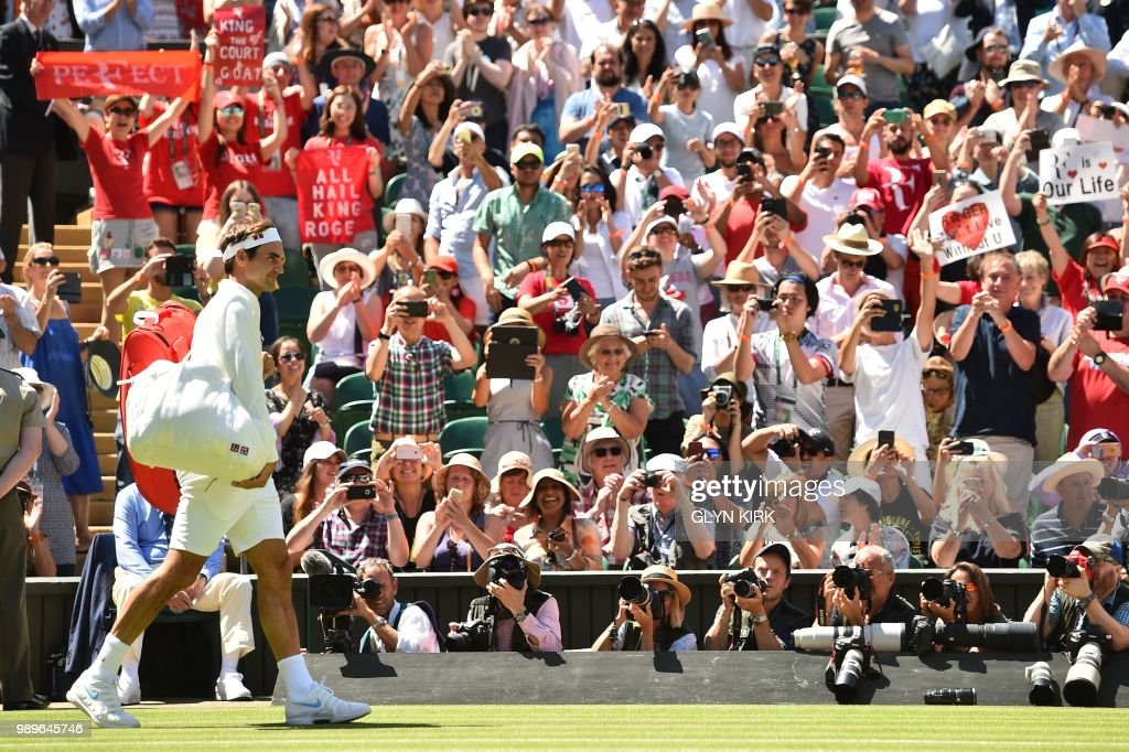 TOPSHOT - Switzerland's Roger Federer arrives on centre court to play Serbia's Dusan Lajovic in their men's singles first round match on the first day of the 2018 Wimbledon Championships at The All England Lawn Tennis Club in Wimbledon, southwest London, on July 2, 2018. (Photo by Glyn KIRK / AFP) / RESTRICTED