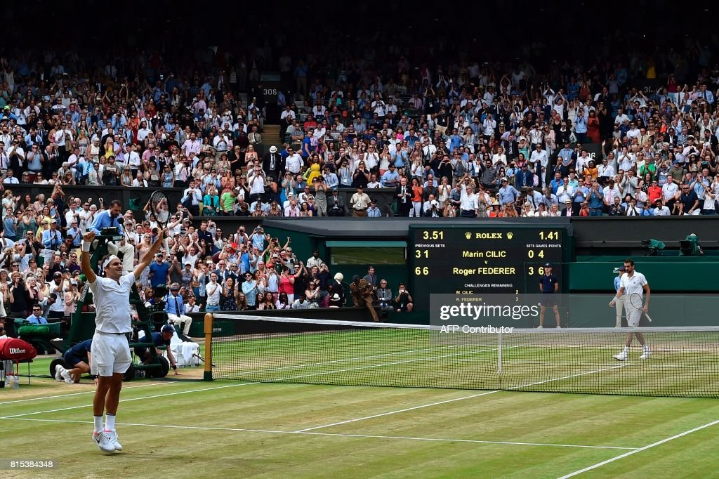 Switzerland's Roger Federer (L) celebrates after winning against Croatia's Marin Cilic during their men's singles final match on the last day of the 2017 Wimbledon Championships at The All England Lawn Tennis Club in Wimbledon, southwest London, on July 16, 2017. Roger Federer won 6-3, 6-1, 6-4. / AFP PHOTO / Glyn KIRK / RESTRICTED