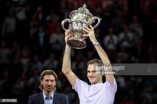Switzerland's Roger Federer celebrates as he raises the trophy after his victory against Argentina's Juan Martin Del Potro in their final game at the...