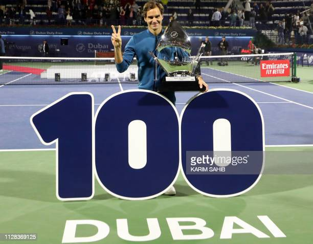 TOPSHOT Switzerland's Roger Federer celebrates with the trophy after winning the final match at the ATP Dubai Tennis Championship in the Gulf emirate...