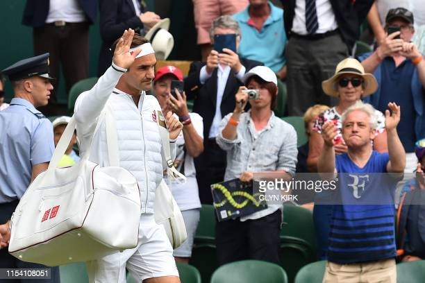 Switzerland's Roger Federer comes on court as spectators including Britain's Speaker of the House of Commons John Bercow applaud to play against...
