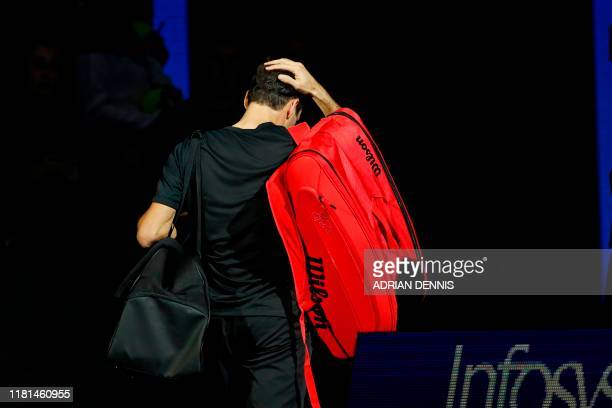 TOPSHOT Switzerland's Roger Federer gestures as he leaves the arena after his straight sets defeat to Austria's Dominic Thiem in their men's singles...