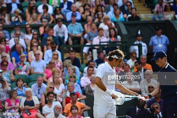 Switzerland's Roger Federer get a new racket during his men's singles semifinal match against Canada's Milos Raonic on day 11 of the 2014 Wimbledon...