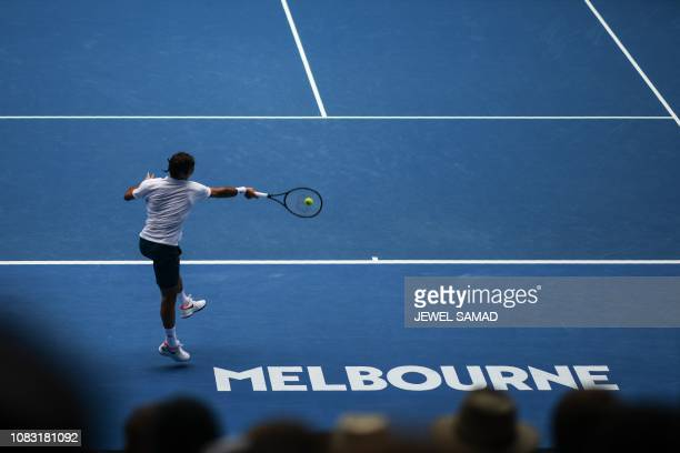Switzerland's Roger Federer hits a return against Britain's Daniel Evans during their men's singles match on day three of the Australian Open tennis...