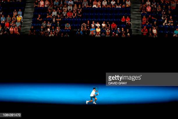 TOPSHOT Switzerland's Roger Federer hits a return against Taylor Fritz of the US during their men's singles match on day five of the Australian Open...