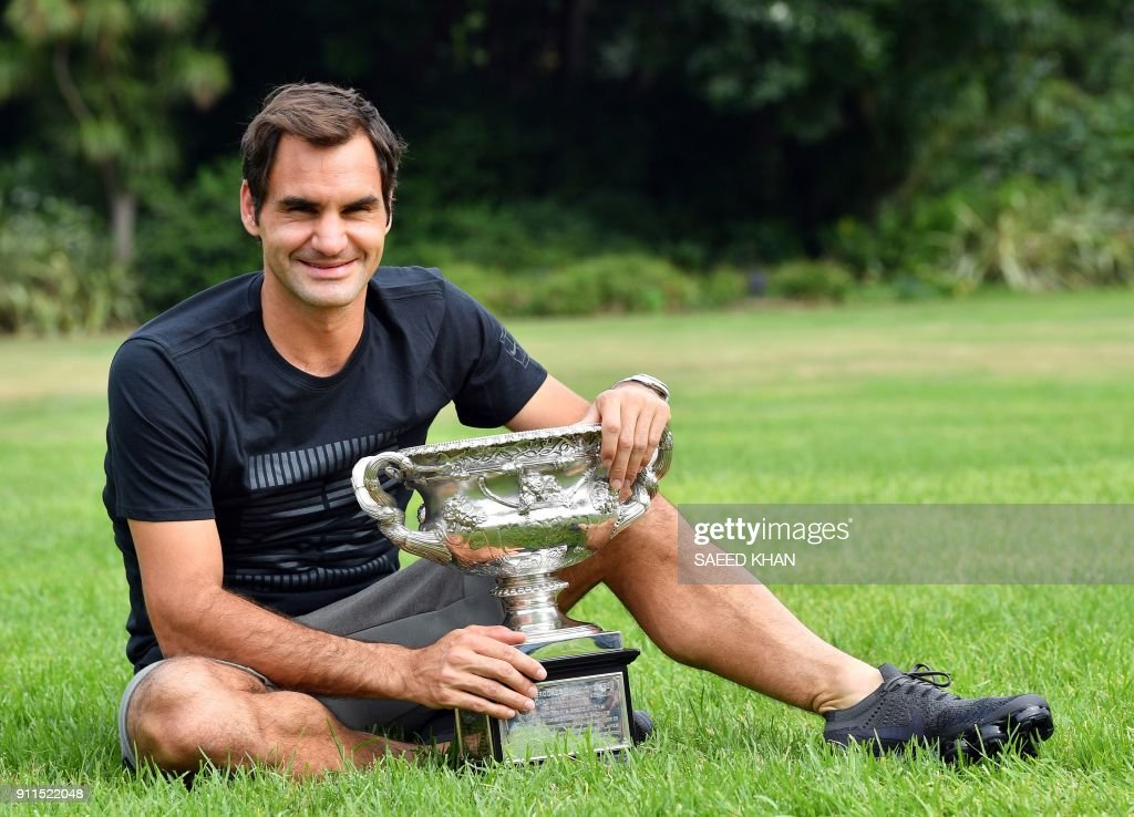 Switzerland's Roger Federer holds the Australia Open trophy at Government House as he poses for pictures following his win in the Australian Open in Melbourne on January 29, 2018. Federer defeated Croatia's Marin Cilic in their men's singles final match on day 14 of the Australian Open tennis tournament. / AFP PHOTO / Saeed KHAN / -- IMAGE