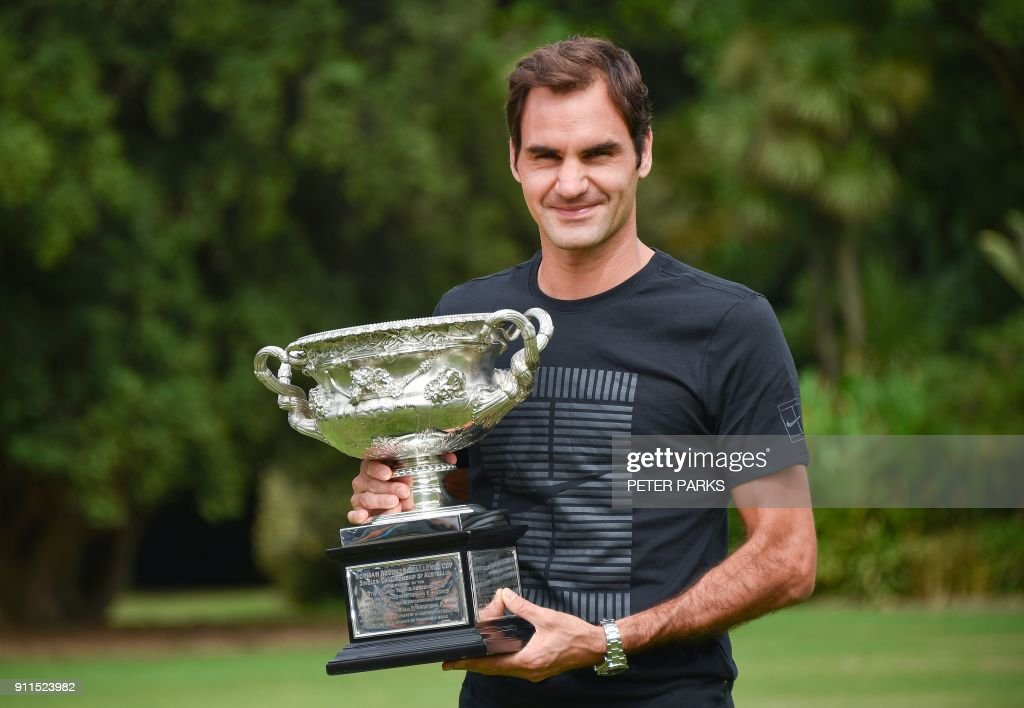 Switzerland's Roger Federer holds the Australia Open trophy at Government House as he poses for pictures following his win in the Australian Open in Melbourne on January 29, 2018. Federer defeated Croatia's Marin Cilic in their men's singles final match on day 14 of the Australian Open tennis tournament. /