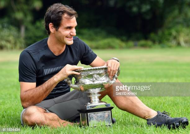 Switzerland's Roger Federer holds the Australia Open trophy at Government House as he poses for pictures following his win in the Australian Open in...