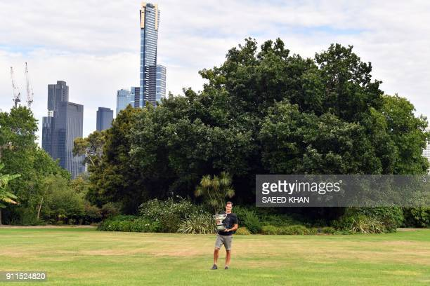 TOPSHOT Switzerland's Roger Federer holds the Australia Open trophy at Government House as he poses for pictures following his win in the Australian...