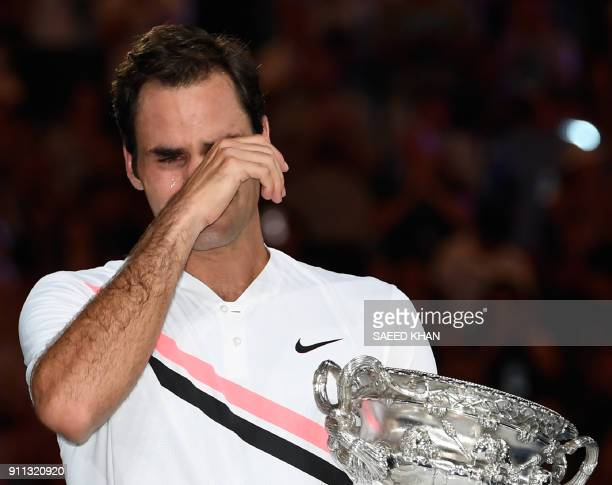 Switzerland's Roger Federer holds the winner's trophy after beating Croatia's Marin Cilic in their men's singles final match on day 14 of the...