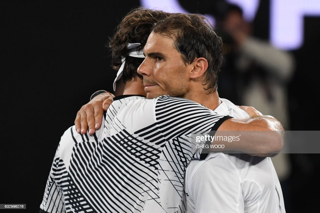TOPSHOT - Switzerland's Roger Federer (R) hugs Spain's Rafael Nadal after winning the men's singles final on day 14 of the Australian Open tennis tournament in Melbourne on January 29, 2017. / AFP / Greg Wood / IMAGE