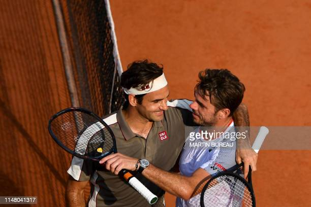 TOPSHOT Switzerland's Roger Federer hugs Switzerland's Stanislas Wawrinka after winning during their men's singles quarterfinal match on day ten of...
