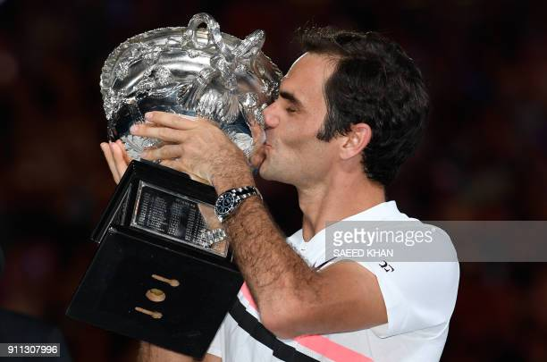 TOPSHOT Switzerland's Roger Federer kisses the winner's trophy after beating Croatia's Marin Cilic in their men's singles final match on day 14 of...
