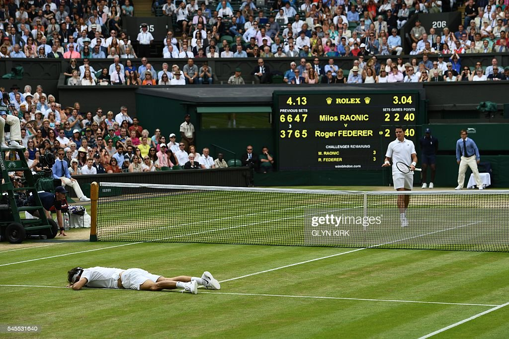 Switzerland's Roger Federer lies on court after falling while trying to return to Canada's Milos Raonic during their men's semi-final match on the twelfth day of the 2016 Wimbledon Championships at The All England Lawn Tennis Club in Wimbledon, southwest London, on July 8, 2016. / AFP / GLYN