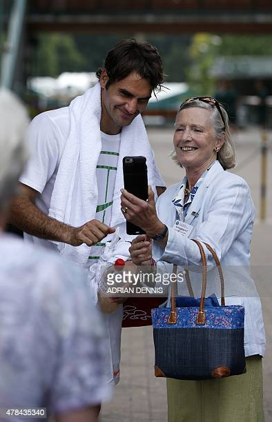 Switzerland's Roger Federer poses for a photograph following a practice session ahead of the 2015 Wimbledon Championships at the All England Tennis...
