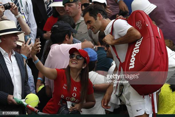 """Switzerland's Roger Federer poses for a """"selfie"""" photograph as he leaves the court after winning against Bulgaria's Grigor Dimitrov during their..."""
