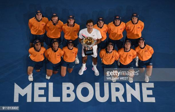 Switzerland's Roger Federer poses with ballboys as he celebrates with the trophy after beating Croatia's Marin Cilic in their men's singles final...