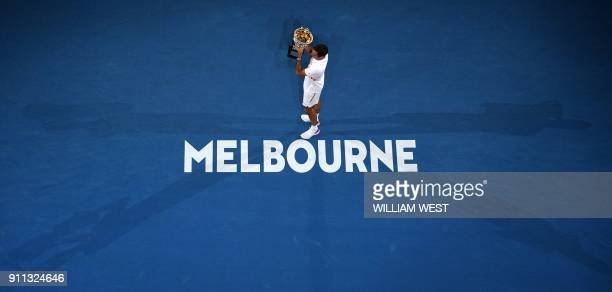 TOPSHOT Switzerland's Roger Federer poses with the trophy as he celebrates beating Croatia's Marin Cilic in their men's singles final match on day 14...
