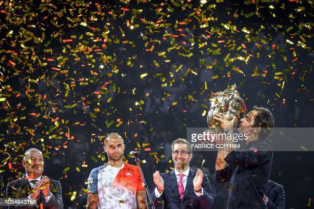 TOPSHOT Switzerland's Roger Federer raises the trophy after his victory against Romania's Marius Copil during their final match at the Swiss Indoors...