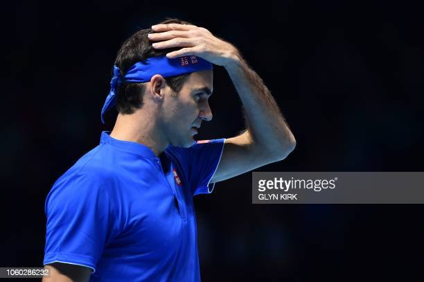 TOPSHOT Switzerland's Roger Federer reacts while playing Japan's Kei Nishikori during their singles round robin match on day one of the ATP World...