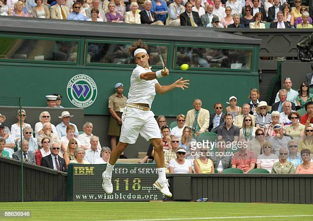 Switzerland's Roger Federer returns a ball to Taiwan's Yen-Hsun Lu during their first round match of the 2009 Wimbledon tennis championships at the...
