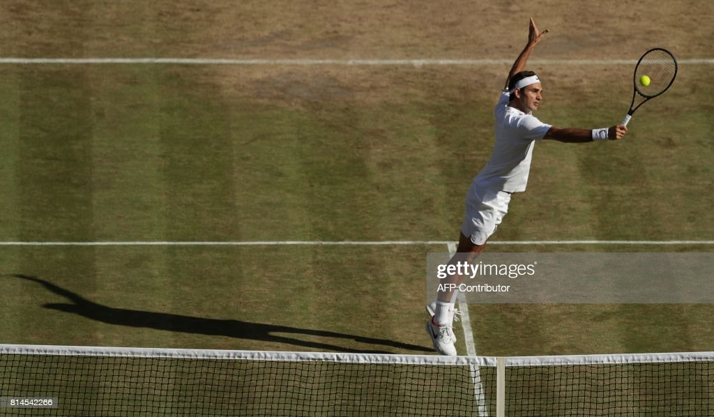 TOPSHOT - Switzerland's Roger Federer returns against Czech Republic's Tomas Berdych during their men's singles semi-final match on the eleventh day of the 2017 Wimbledon Championships at The All England Lawn Tennis Club in Wimbledon, southwest London, on July 14, 2017. / AFP PHOTO / POOL / Tim IRELAND / RESTRICTED
