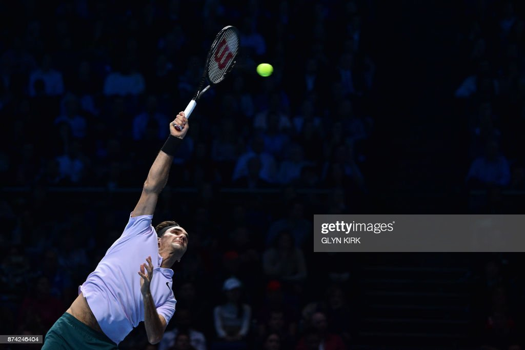 TOPSHOT - Switzerland's Roger Federer returns against Germany's Alexander Zverev during their men's singles round-robin match on day three of the ATP World Tour Finals tennis tournament at the O2 Arena in London on November 14, 2017. / AFP PHOTO / Glyn KIRK