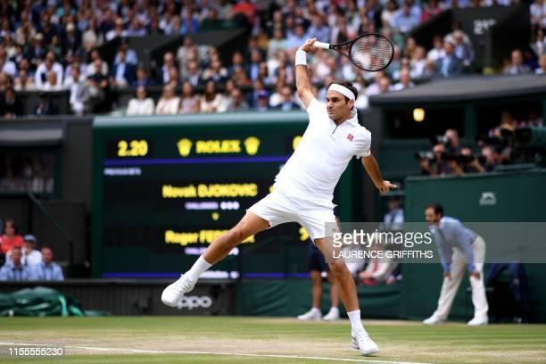 TOPSHOT Switzerland's Roger Federer returns against Serbia's Novak Djokovic during their men's singles final on day thirteen of the 2019 Wimbledon...
