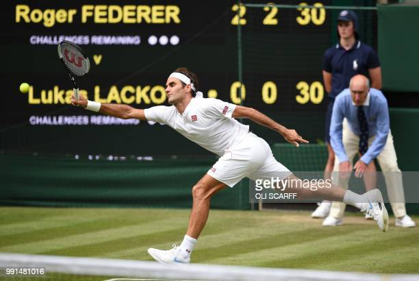 Switzerland's Roger Federer returns against Slovakia's Lukas Lacko during their men's singles second round match on the third day of the 2018...