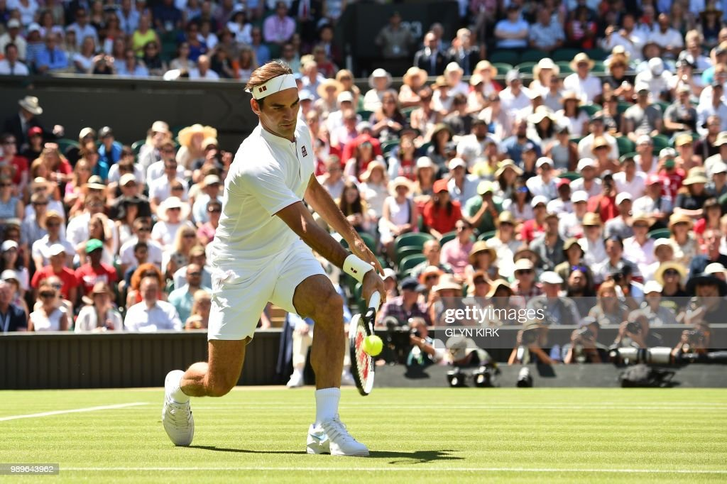 TOPSHOT - Switzerland's Roger Federer returns to Serbia's Dusan Lajovic during their men's singles first round match on the first day of the 2018 Wimbledon Championships at The All England Lawn Tennis Club in Wimbledon, southwest London, on July 2, 2018. (Photo by Glyn KIRK / AFP) / RESTRICTED