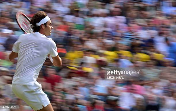 Switzerland's Roger Federer returns to Spain's Roberto Bautista Agut during their men's singles fourth round match on day seven of the 2015 Wimbledon...
