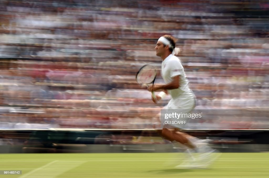 TOPSHOT - Switzerland's Roger Federer runs to play a return against Slovakia's Lukas Lacko during their men's singles second round match on the third day of the 2018 Wimbledon Championships at The All England Lawn Tennis Club in Wimbledon, southwest London, on July 4, 2018. - Federer won the match 6-4, 6-4, 6-1. (Photo by Oli SCARFF / AFP) / RESTRICTED
