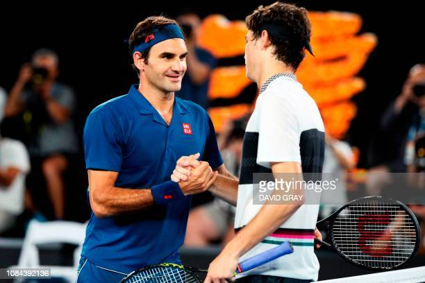 TOPSHOT Switzerland's Roger Federer shakes hand Taylor Fritz of the US during their men's singles match on day five of the Australian Open tennis...