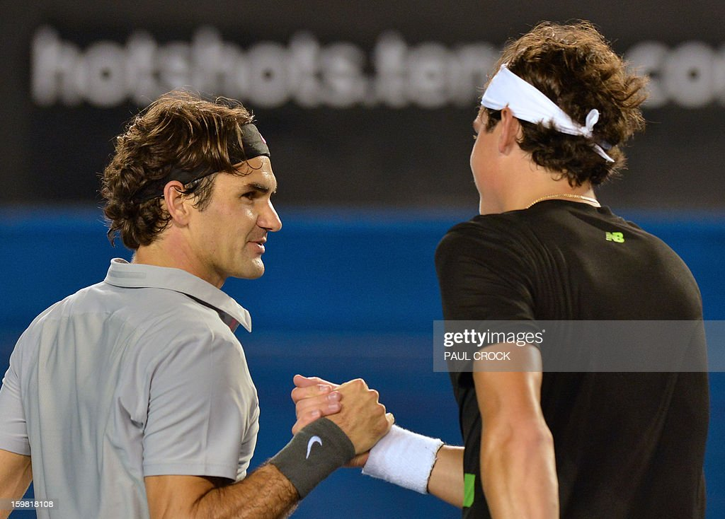Switzerland's Roger Federer (L) shakes hands after victory in his men's singles match against Canada's Milos Raonic on the eighth day of the Australian Open tennis tournament in Melbourne on January 21, 2013.