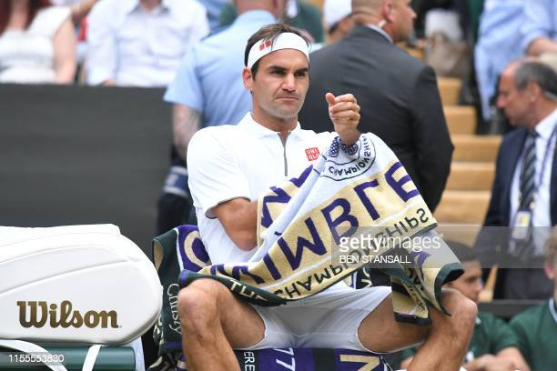 Switzerland's Roger Federer sits in the break between games against Serbia's Novak Djokovic during the men's singles final on day thirteen of the...