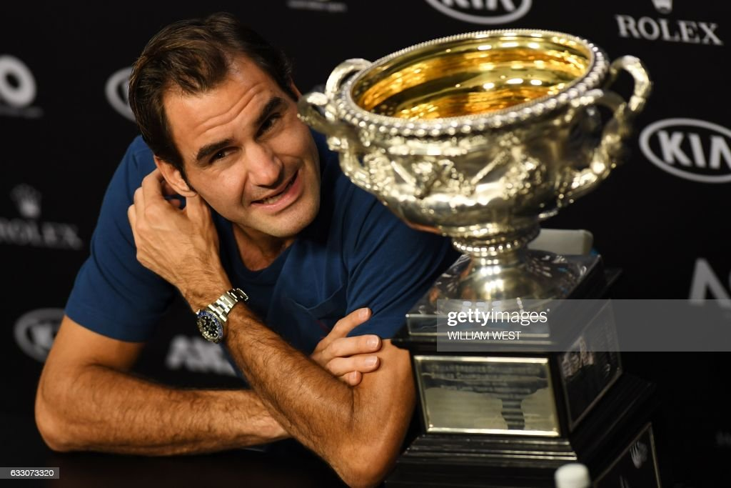 Switzerland's Roger Federer speaks next to the championship trophy during a press conference after his victory against Spain's Rafael Nadal in the men's singles final on day 14 of the Australian Open tennis tournament in Melbourne on January 30, 2017. / AFP / WILLIAM