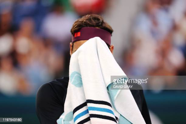 Switzerland's Roger Federer uses a towel during a break in his men's singles semifinal match against Serbia's Novak Djokovic on day eleven of the...