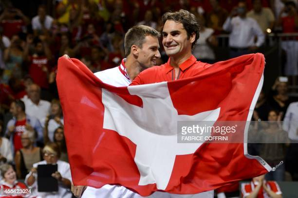 Switzerland's Roger Federer waves his national flag next to teammate Michael Lammer as they celebrate winning the Davis Cup semifinal between...