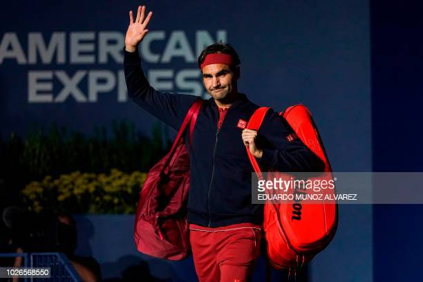 Switzerland's Roger Federer waves to the crowd as he walks onto the court for his 2018 US Open Men's Singles tennis match against Australia's John...