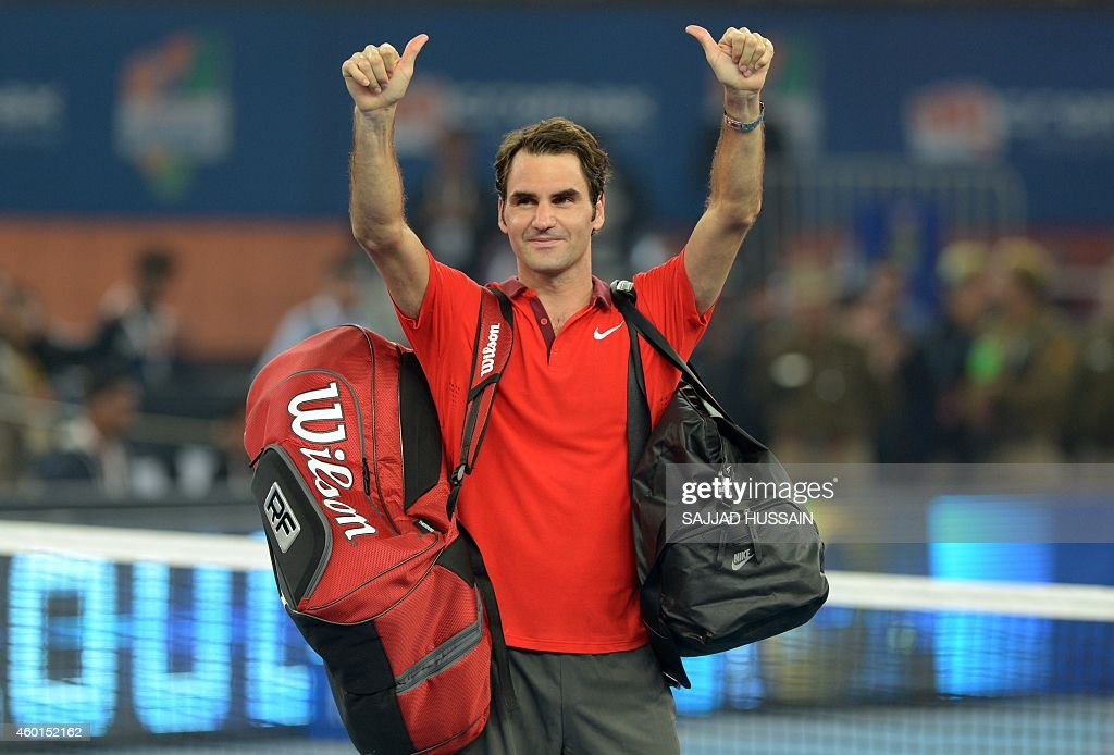 Switzerland's Roger Federer waves to the crowd at the end of his Men's single tennis match against Serbia's Novak Djokovic at the International Premier Tennis League (IPTL) match in New Delhi on December 8, 2014.