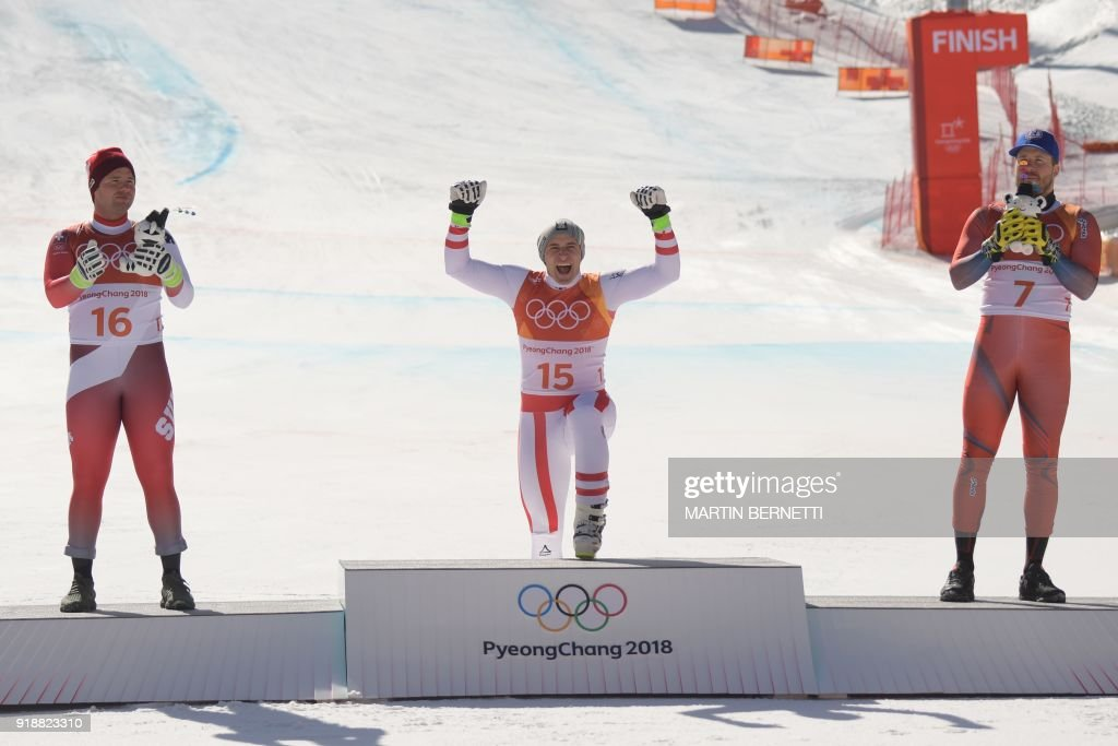 Switzerland's second place winner Beat Feuz, Austria's winner Matthias Mayer and Norway's third place Kjetil Jansrud celebrate on the podium during the victory ceremony at the end of the Men's Super-G at the Jeongseon Alpine Center during the Pyeongchang 2018 Winter Olympic Games in Pyeongchang on February 16, 2018. / AFP PHOTO / Martin BERNETTI