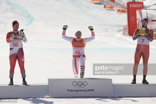 Switzerland's second place winner Beat Feuz Austria's winner Matthias Mayer and Norway's third place Kjetil Jansrud celebrate on the podium during...