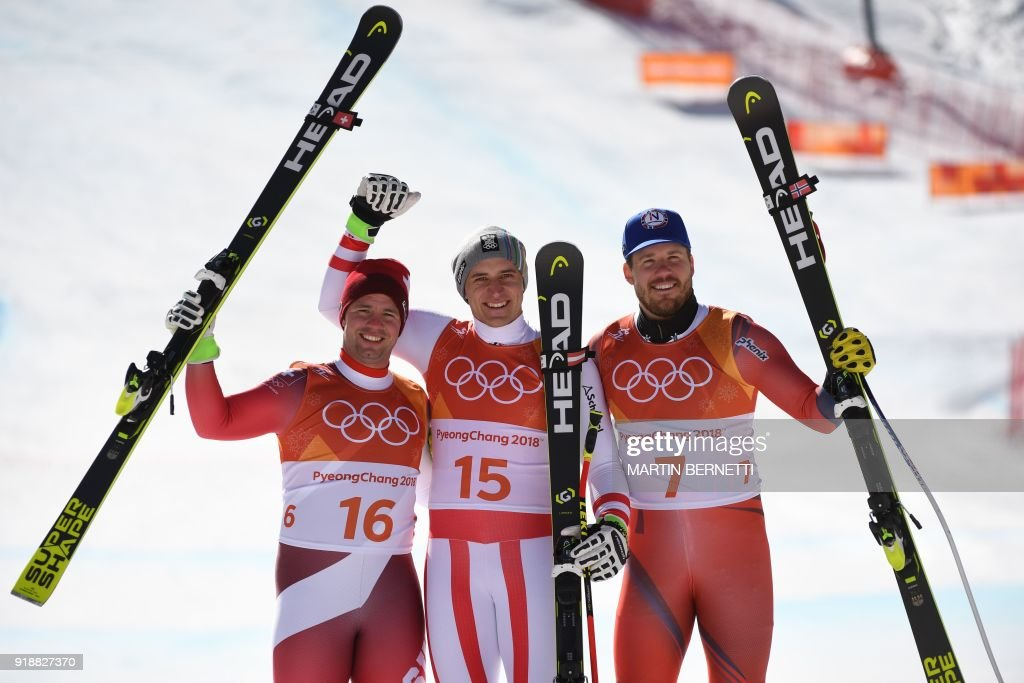 TOPSHOT - (L-R) Switzerland's second place winner Beat Feuz, Austria's winner Matthias Mayer and Norway's third place Kjetil Jansrud pose on the podium during the victory ceremony at the end of the Men's Super-G at the Jeongseon Alpine Center during the Pyeongchang 2018 Winter Olympic Games in Pyeongchang on February 16, 2018. / AFP PHOTO / Martin BERNETTI