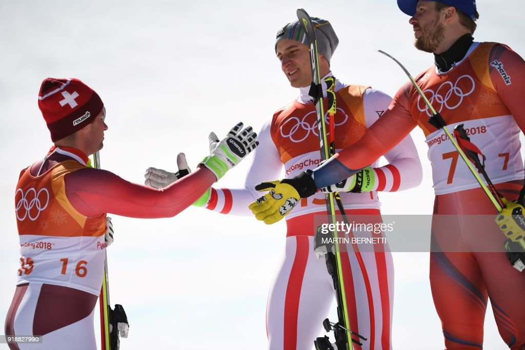 Switzerland's second place winner Beat Feuz, Austria's winner Matthias Mayer and Norway's third place Kjetil Jansrud shake hands on the podium during the victory ceremony at the end of the Men's Super-G at the Jeongseon Alpine Center during the Pyeongchang 2018 Winter Olympic Games in Pyeongchang on February 16, 2018. / AFP PHOTO / Martin BERNETTI