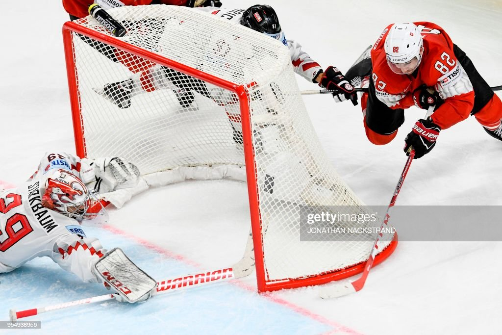 Switzerland's Simon Moser (R) strikes behind Austria's goalie Bernhard Starkbaum (L) during the group A match Switzerland vs Austria of the 2018 IIHF Ice Hockey World Championship at the Royal Arena in Copenhagen, Denmark, on May 5, 2018.